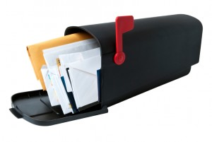 American-style mailbox full with letters and miscellaneous mail, flag raised. Studio shot, isolated on white background, saved with clipping path